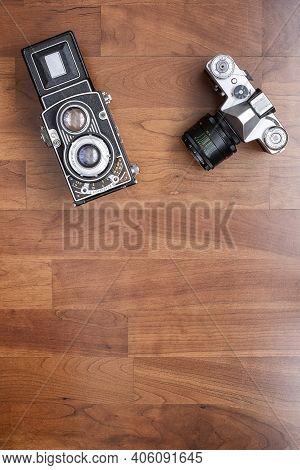 An Old 35mm Reflex Camera, And An Old Medium Format Twin Lens Reflex Camera, Seen From Above Vertica