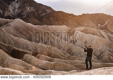 Man Taking Picture On A Mobile Phone At Zabriskie Point In Death Valley National Park, California, U