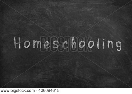 Homeschooling. Word Homeschooling Written On An Old Blackboard.