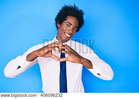 Handsome african american man with afro hair wearing business shirt and tie smiling in love doing heart symbol shape with hands. romantic concept.
