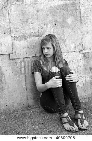Sad teenage girl sitting on the ground in alleyway.