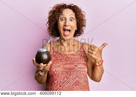 Beautiful middle age mature woman drinking mate infusion pointing thumb up to the side smiling happy with open mouth