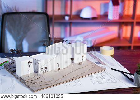 Constructions Models Near Blueprint On Desk In Architectural Bureau