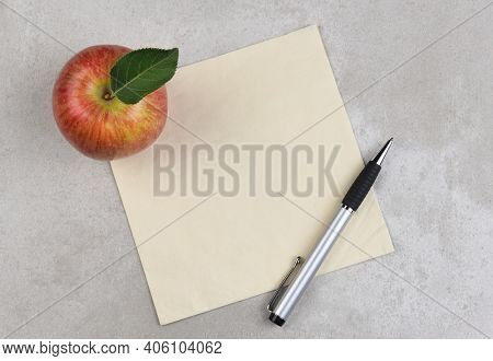 An apple, pen, and napkin on a gray mottled surface. Room for copy or doodle on the napkin.