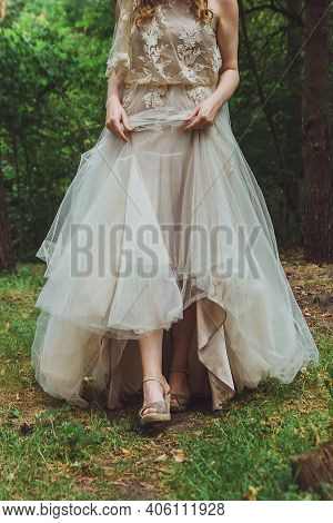 Cropped Photo Of Young Blonde Bride Walking In The Forest, Holding The Bottom Of The Long Beige Wedd