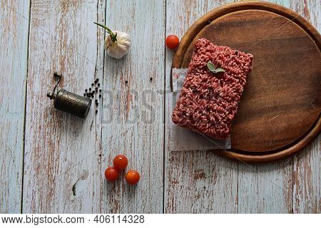 Minced Meat, Fresh Raw Beef Whit Black Pepper, Mint, Basil And Garlic Served On Plate On Rustic Wood