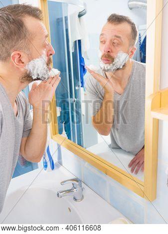 Man Applying Shaving Foam Cream On His Face, Standing In Bathroom, Looking At Mirror, Preparing To S