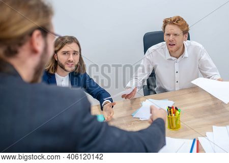 Disgruntled Indignant Men At Table In Office