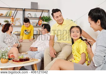 Little Children Talking To Parents And Grandparents During Family Gathering At Home