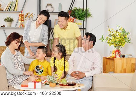 Vietnamese Family Gathered At Home To Celebrate Lunar New Year And Wish Luck To Little Children In T