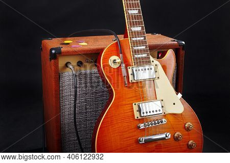 Combo Amplifier For Guitar With Guitar On The Black Background.