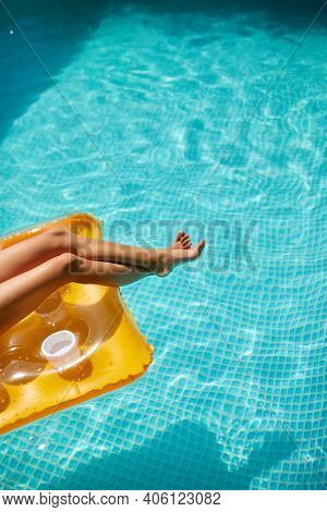 Little Girl In Sunglasses Relaxing In Swimming Pool, Enjoying Suntans, Wims On Inflatable Yellow Mat