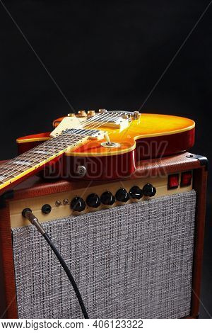 Tube Amplifier For Guitar With Honey Sunburst Guitar On The Black Background.