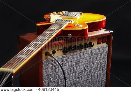 Brown Combo Amplifier For Electric Guitar With Honey Sunburst Guitar On The Black Background.