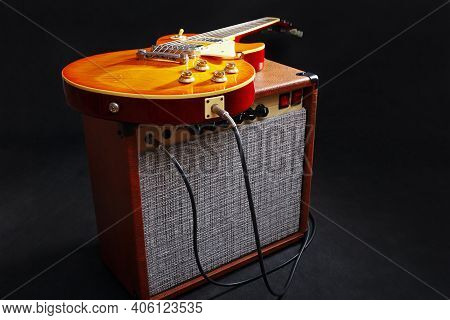 Brown Guitar Amplifier With Honey Sunburst Guitar On The Black Background.
