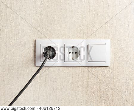 The Plug Is Plugged Into An Electrical Outlet On The Wall. Copy Space.