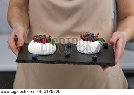 Cake Anna Pavlova On Black Tray In The Pastry Chef Hands. Meringue Cake With Fresh Berries.