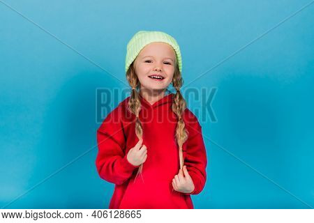Little Blonde Girl, She Laughing, Sitting On Floor, Posing Isolated On Blue. Childhood, Fashion.