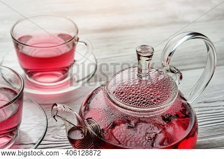 Misted Teapot And Cups Of Tea Close-up. Hibiscus Tea In A Glass Teapot.