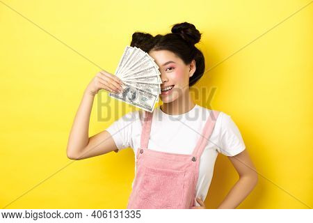 Shopping. Beautiful Asian Female Model With Glamour Makeup, Cover Half Of Face With Money Dollar Bil
