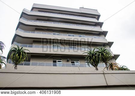 Upward View Of Tall Residential Building Against Cloudy Sky