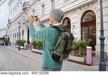 Traveler With Backpack Taking Photo In Foreign City During Vacation