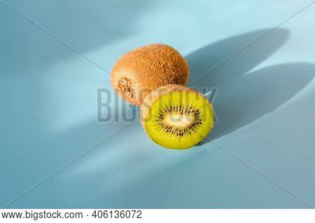 Cut And Whole Kiwi With Shadow On Blue Background. Selective Focus. Minimalism