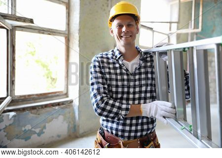 Professional Constructor With Ladder In Old Building