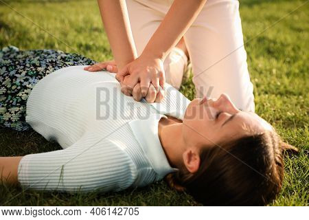 Woman Doing Cardiac Massage To Unconscious Person With Heart Attack On Green Lawn