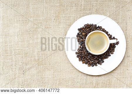 Heart Symbol Made Of Roasted Coffee Beans And A Coffee Cup On A Burlap Cloth Background