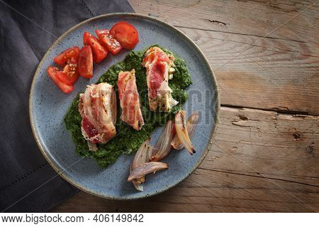 Fried  Chicken Breast Fillet Rolled In Bacon On Cream Spinach With Roasted Onions And Tomatoes On A