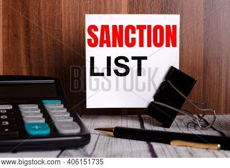 Sanction List Is Written On A White Card On A Wooden Background Next To A Calculator And Pen.