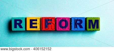 The Word Reform Is Written On Multicolored Bright Wooden Cubes On A Light Blue Background