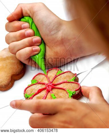 Cookies In The Left Hand. Pastry Bag With Green Sweet Icing In The Right Hand. Girl Draws A Pattern