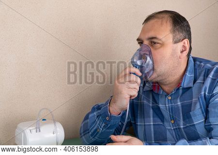 Adult Person Makes Inhalations With The Help Of Nebulizer. Patient Breathes Through An Oxygen Mask.