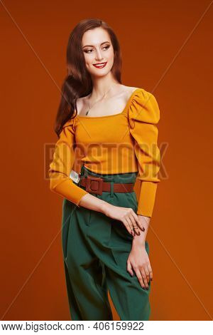 Portrait of a beautiful smiling girl in colorful clothes on orange background. Fashion shot. Bright colors in clothing.