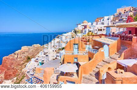 Oia (Ia) town by the sea in Santorini island on sunny summer day, Greece. Greek landscape - cityscape