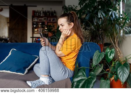 Sad Young Lonely Woman Yellow Tshirt In Depression Looking At Phone Gets Bad News, Sitting On Sofa,