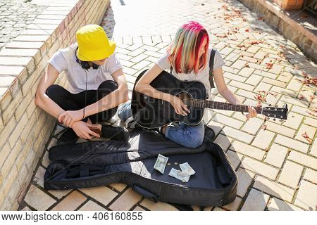 Happy Young People Couple Guy And Girl Playing Acoustic Guitar. Trending Creative Teenagers Sitting