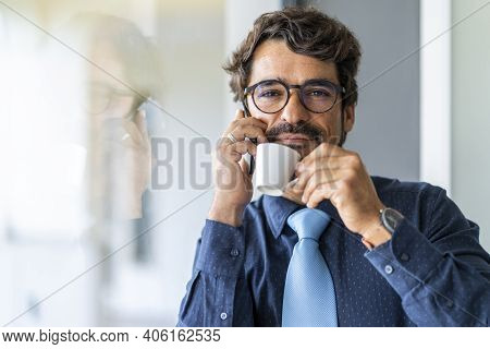 Businessman Wearing Glasses, Talking On The Phone While Holding A Cup Of Coffee And Through The Wind
