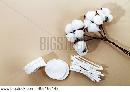 Fluffy Cotton Flower Cotton Pads And Cotton Swabs On Beige Background With Copy Space. Hygienic Disp