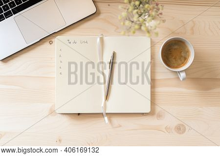 Top View Blank Paper Notebook With To Do List, Flowers, Laptop Keyboard, Cup Of Coffee And Pen. Desk