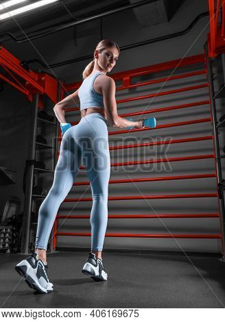Beautiful Tall Blonde Posing In The Gym With Dumbbells In Her Hands Against The Background Of The Wa