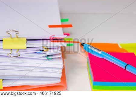 Close-up Of A Pile Of Paper With Colored Post Its And A Pen. Information Overload Conceptclose-up Of