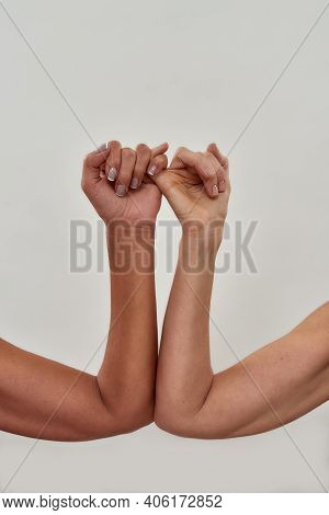 Close Up Shot Of Pinky Swear. Promise Hand Gesture Isolated Over Light Background. Vertical Shot