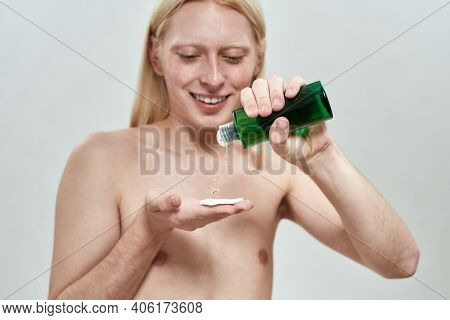 Selective Focus On Facial Tonic In Hands Of Young Caucasian Blond Man With Long Hair Standing On Lig
