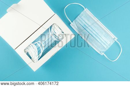 Directly Above View Of Medical Face Masks In Dispenser Box On Blue Background