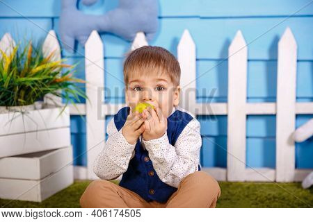 Happy Caucasian Child Eating And Biting A Green Apple. Funny Blonde Boy Eating Apple At Home. Boy Ea