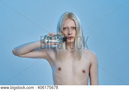 Young Caucasian Man With Long Blond Hair Holding Bottle With Mouthwash Liquid While Standing On Blue