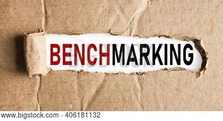 Benchmarking. Text On White Paper On Torn Paper Background